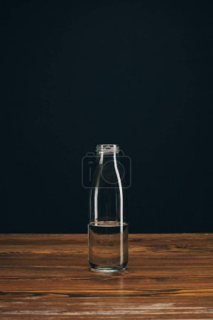 glass bottle with mineral water on brown table on black