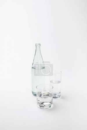 two different glasses and bottle with calm water isolated on white