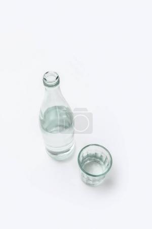 overhead view of bottle and glass with water isolated on white