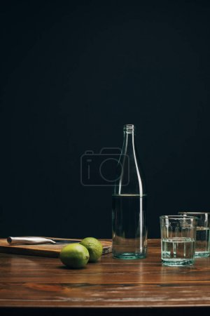 Bottle and glasses with water and limes on brown table