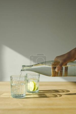 cropped image of woman pouring water from bottle into transparent glass