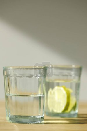 close up view of glass with water and glass with lemonade
