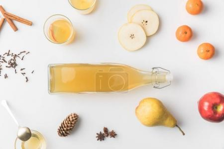 top view of bottle of cider with ingredients around on white tabletop