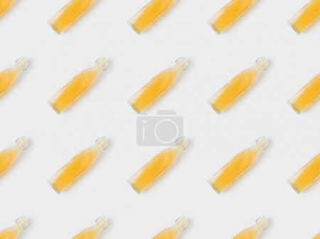 pattern of apple cider bottles on white surface