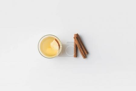 top view of glass of apple cider with cinnamon sticks on white surface