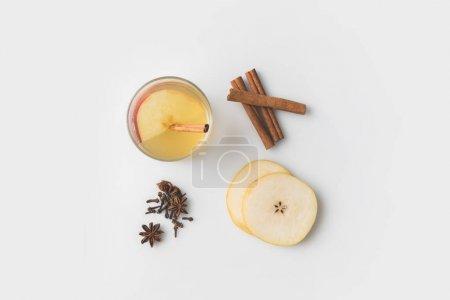 Ansicht der Apfelmost-Komposition mit Gewürzen und Birnenscheiben auf weißer Tischplatte