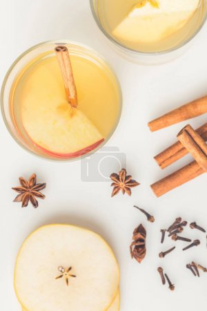 top view of refreshing cider with spices on white surface