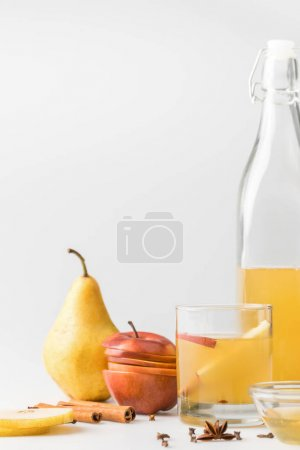 cider in bottle with glass and fruits on white surface