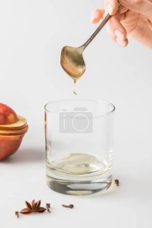 cropped shot of woman pouring honey in glass from spoon on white table