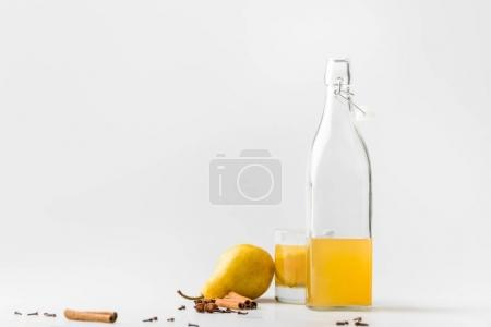 bottle of delicious of pear cider with spices on white table