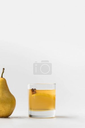 glass of refreshing pear cider with cinnamon on white