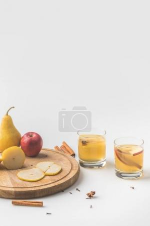 glasses of cider with apple and pear on wooden board on white