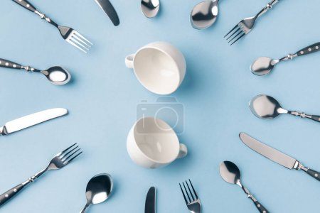 top view of tea cups surrounded by flatware isolated on blue