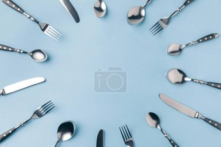 flat lay of flatware frame with copy space isolated on blue