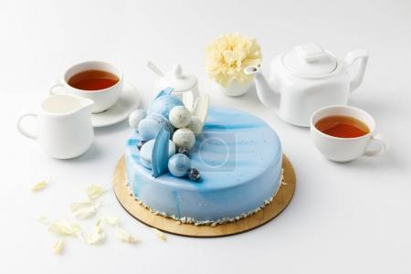 Photo for Blue tasty cake on chopping board with tea and flower isolated on white - Royalty Free Image