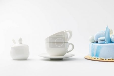 blue tasty cake on chopping board with tea cups isolated on white