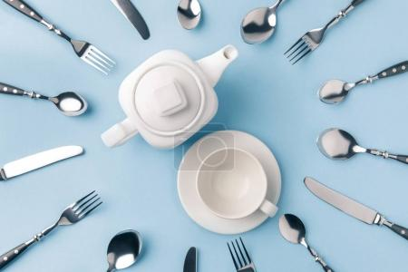 top view of teapot with cup on plate, surrounded by flatware isolated on blue
