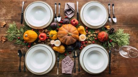 Photo pour Vue du dessus de la table avec divers fruits et citrouilles sur la table d'automne couverte de branches de sapin - image libre de droit