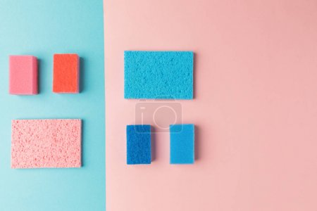 top view of colorful washing sponges, on pink and blue