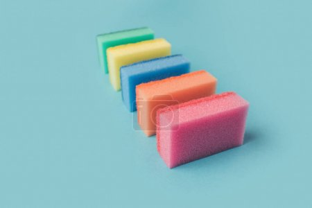row of colorful washing kitchen sponges, on blue