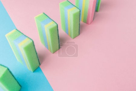 line of colorful washing kitchen sponges, on blue and pink