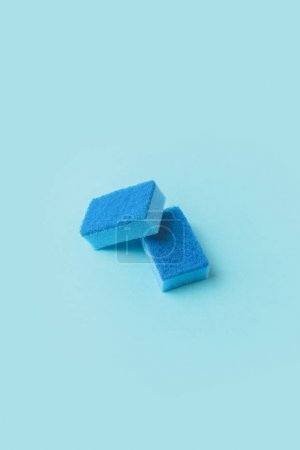 two blue washing kitchen sponges, on blue