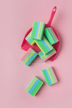 top view of colorful washing sponges in scoop, isolated on pink