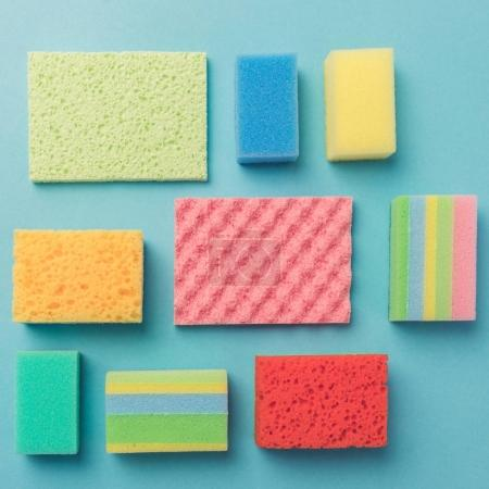 top view of background with colorful washing sponges, on blue