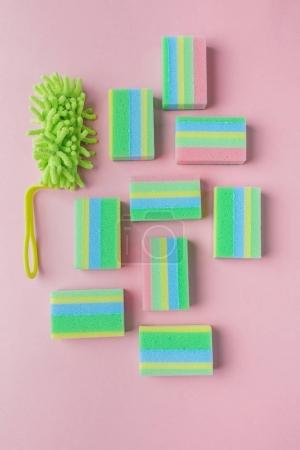 top view of colorful washing sponges and brush, on pink