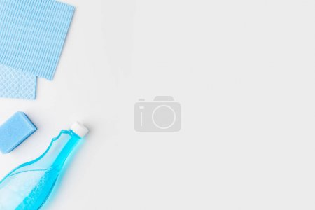 top view of blue washing sponges and spray bottle, isolated on white