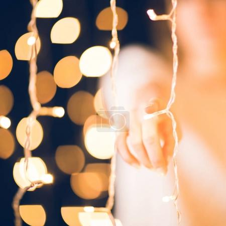 cropped shot of woman pointing at camera behind holiday garland