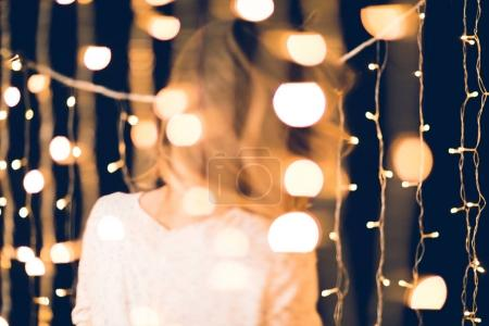 beautiful christmas garland with blurred woman moving on background