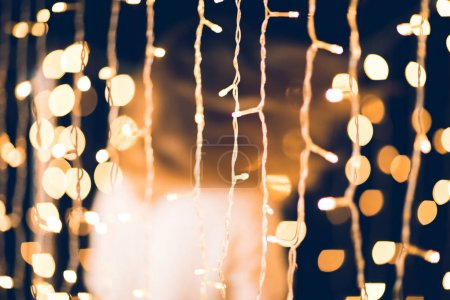 golden christmas garland with blurred woman moving on background