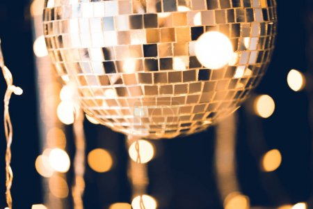 close-up shot of glossy disco ball on black background with garland hanging around