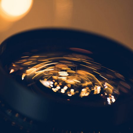 close-up shot of holiday lights reflecting in glass of camera lens