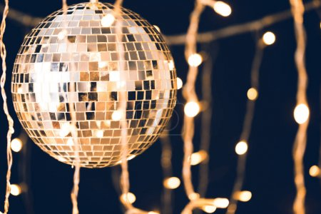 glossy disco ball with garland on black background