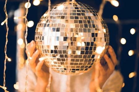 woman touching disco ball with beautiful garlands around
