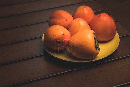 yellow plate with orange persimmons on brown table