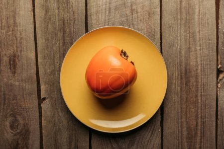 top view of persimmon on yellow plate on wooden table