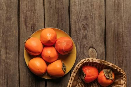 top view of yummy persimmons on plate and in basket on table
