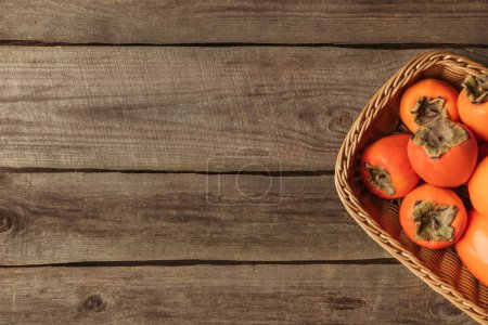 top view of straw basket with ripe persimmons on wooden table