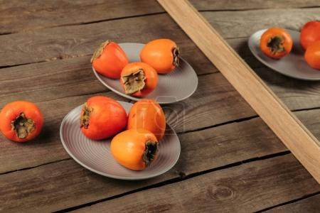 ripe persimmons on plates reflecting in the mirror