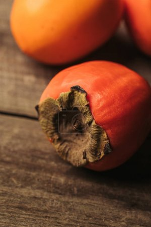 close up view of ripe persimmons on wooden table