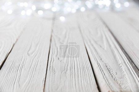 festive christmas bokeh lights on white wooden surface