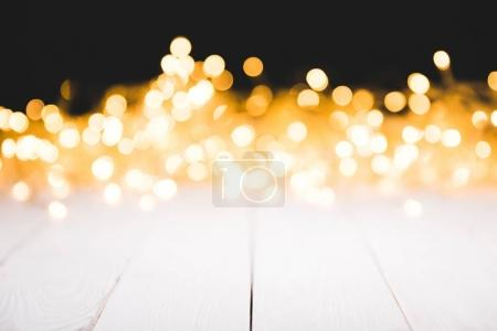 festive bokeh lights on white wooden surface, christmas background