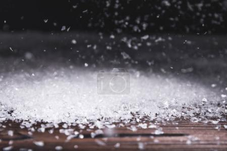 winter holiday background with snow falling on wooden surface