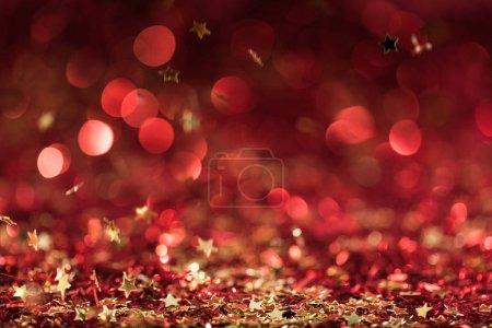 Photo pour Texture de Noël avec des étoiles de confettis brillantes rouges tombantes - image libre de droit