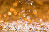 christmas texture with falling golden and silver shiny confetti stars with bokeh