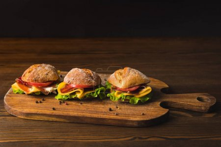 overhead view of three sandwiches with cheese on wooden board