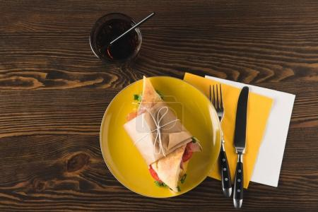 Photo for Top view of panini on yellow plate with fork and knife on napkins - Royalty Free Image